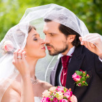 Bridal pair kissing under veil at wedding