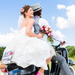 Wedding groom and bride driving motor scooter having fun, a just married sign attached