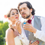 Wedding bride and groom blowing bubbles outside on field